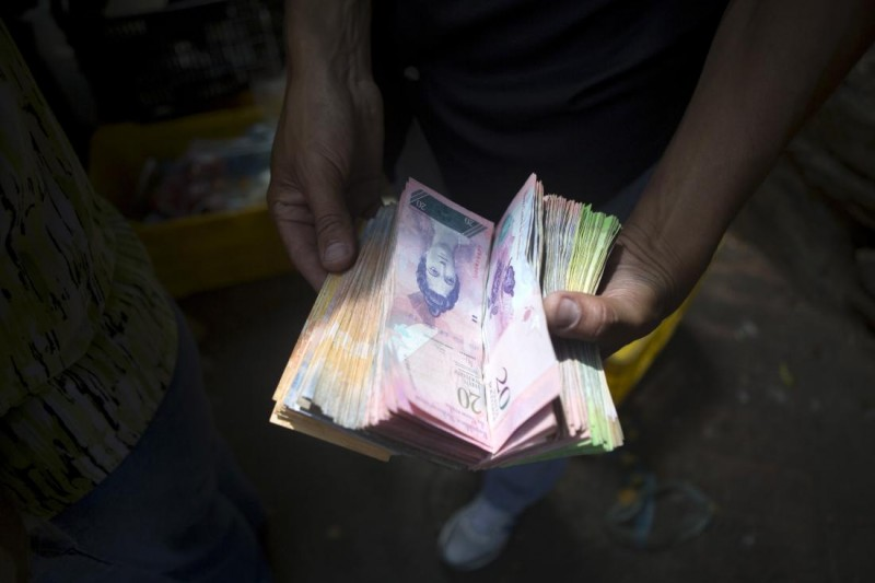 A man displays bolivar notes that he carries to pay for goods at a street market in Caracas